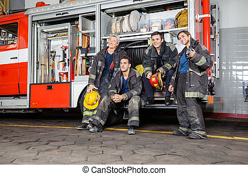 Team Of Thoughtful Firefighters By Firetruck - Team of...