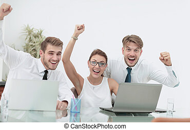 Team of three work colleagues with their arms raised in celebrat