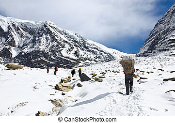 team of trekkers and porters in Himalaya mountains