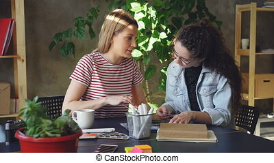 Team of two creative designers are looking at pictures and talking about them while sitting together at desk. Pan shot of modern informal office. Friendly working atmosphere.
