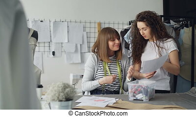 Team of two creative designers is choosing color of sewing threads for garment drawn on sketch. Women are reeling bobbins in and out, talking and gesturing.