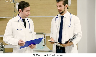 Team of two doctors talking in the hospital room with folders in hands