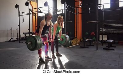 Team of two fitness women doing deadlift exercise in gym