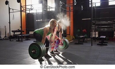 Team of two fitness women doing deadlift training together, giving high five and smiling in gym, slow motion