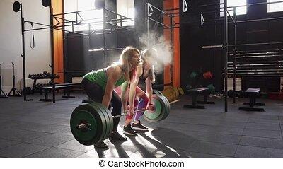 Team of two fitness women doing deadlift training, giving ...