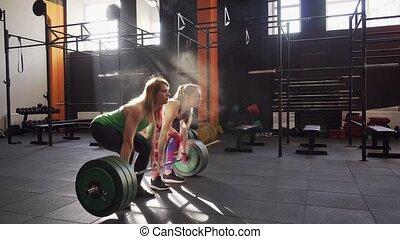 Team of two fitness women doing deadlift workout, giving ...