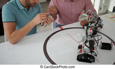 Team of two professional chatting about robotics - Two heads...