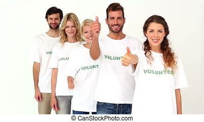 Team of volunteers giving thumbs up to camera on white...