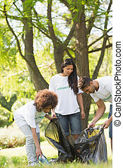 Team of volunteers picking up litter in park - Team of young...