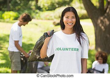 Team of volunteers picking up litter in park
