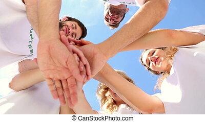 Team of volunteers putting hands together