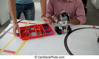 Team of young engineers working on robotic machine