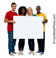 Team of young people holding whiteboard and presenting it to...