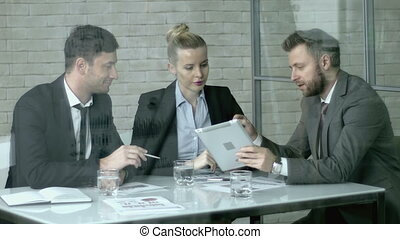 Team Planning - Three business partners discussing strategy...