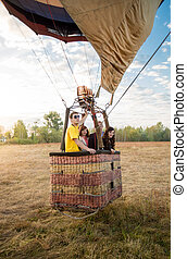 Team preparing to taking off at hot air balloon at meadow -...