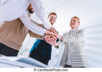 Low angle of people holding hands together