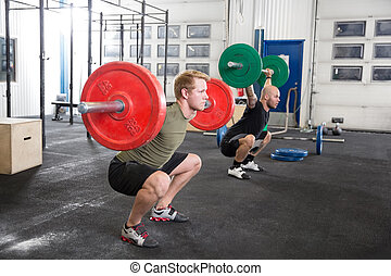 Team trains squats at fitness gym center - Two men taking...