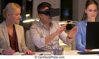 team with virtual reality headset at night office