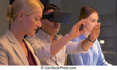 team with virtual reality headset at night office -...
