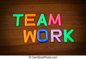 Team work in colorful toy letters on wood background