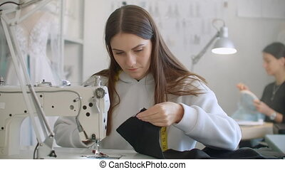 Team work of two tailor and dressmaker who are smile and working on sewing a new collection. The seamstress cuts pattern with scissors and the stylist follows the workflow.