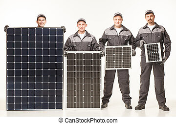 team working with a variety of solar panels white studio...