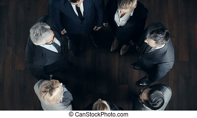 Right from above view of business team of seven team building putting hands on top of each other