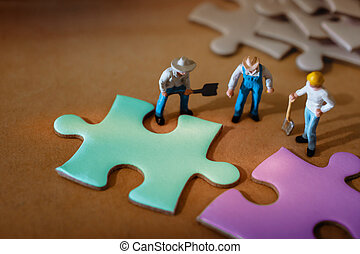 Teamwork, Business Strategy, Connection, Partnership and Team Collaborate Concept.  Group of Miniature Worker Working on Jigsaw Puzzle