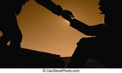 teamwork business travel trip. two men with backpacks hiking help each other silhouette in mountains with sunlight. slow motion video. teamwork friendship hiking help each other trust assistance the silhouette in mountains, sunrise . victory is the way to lifestyle success