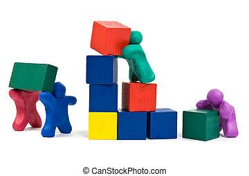 teamwork concept. plasticine people building wooden blocks