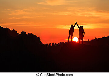 Teamwork couple celebrating in inspiring mountains sunset