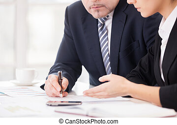 Teamwork. Cropped image of two confident business people discussing something while sitting together at the table
