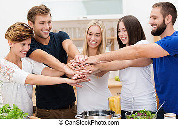 Group of enthusiastic multicultural young friends with happy smiles standing in the kitchen placing their hands in a stack denoting cooperation and teamwork