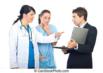 Teamwork having discussion and using laptop - Two doctors...