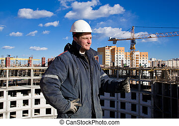 Construction worker at construction site pointing OK hand gesture