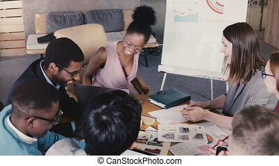 Teamwork in trendy loft business coworking space. Young happy multiethnic creative employees brainstorm together 4K. Multiracial architecture bureau colleagues discuss sales growth perspectives.