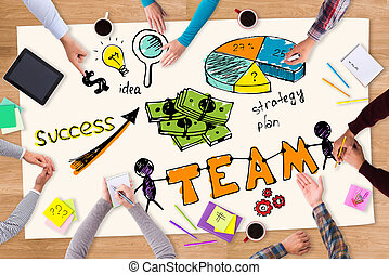Teamwork is a key to success. Top view of paper with colorful sketches laying on the wooden table and people sitting around it