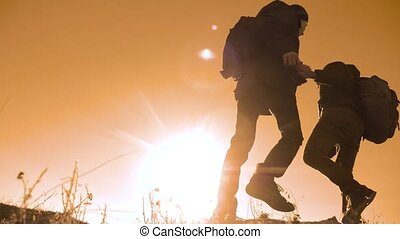 teamwork lifestyle tourists business travel trip lends a helping hand. two men with backpacks hiking help each other silhouette in mountains with sunlight. slow motion video. teamwork friendship hiking help each other trust assistance the silhouette in mountains, sunrise. victory is the way to success