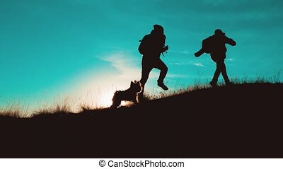 teamwork men run jump from happiness victory walking . two tourists hikers men with backpacks at sunset go hiking trip overcoming difficulties victory success. hikers adventure and the dog go walking. travel mountains silhouette. hikers adventure and the dog go lifestyle
