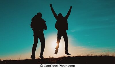 teamwork men run jump from happiness victory walking . two tourists hikers men with backpacks at sunset go hiking trip. hikers adventure and the dog go walking. travel mountains silhouette. hikers lifestyle adventure and the dog go