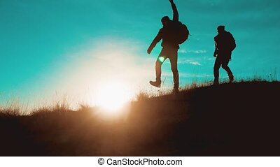 teamwork men run jump from happiness victory walking . two tourists hikers men with backpacks at sunset go hiking trip overcoming difficulties victory success. hikers adventure and dog go walking. travel mountains silhouette. hikers adventure and lifestyle the dog go