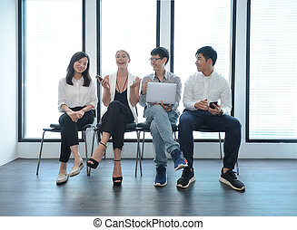 Teamwork of international business people taking to each other in office, multi ethnic