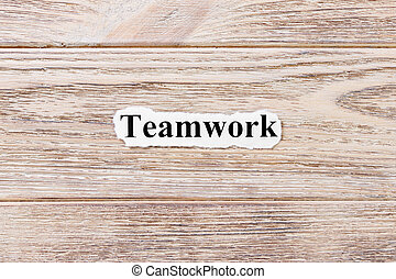 Teamwork of the word on paper. concept. Words of Teamwork on a wooden background