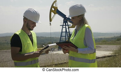 Teamwork of young proactive successful engineers in oilfield industry analyzing engineering project on tablet computer near oil pump unit