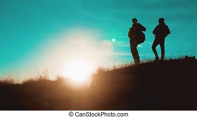 teamwork overcoming difficulties victory success. two tourists silhouette hikers men with backpacks at sunset go hiking trip. hikers adventure and the dog go walking. travel mountains lifestyle silhouette