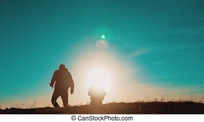teamwork smartphone navigation. two tourists hikers men with backpacks at sunset go hiking trip. hikers adventure and the dog go walking. travel mountains silhouette. lifestyle hikers adventure and the dog go walking