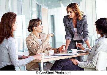 Teamwork - Image of four businesswomen interacting at...