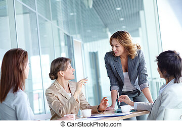 Teamwork - Image of four businesswomen interacting at...