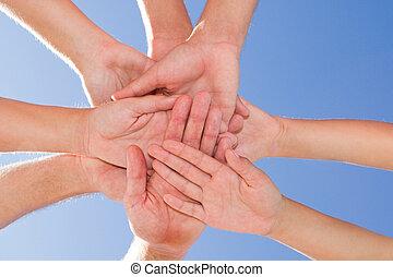 teamwork - four hands together indicating teamwork
