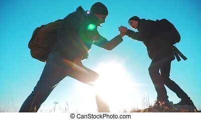 teamwork tourists business travel trip lends a helping hand. two men with backpacks hiking help each other silhouette in mountains with sunlight. lifestyle slow motion video. teamwork friendship hiking help each other trust assistance the silhouette in mountains, sunrise. victory is the way to success